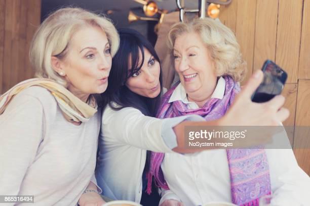 Sozialer Senioren. Zwei ältere Damen und schwarze Haare junge Frau, im Café sitzen, lachen, machen Kaffeepause, die Selfie mit Smartphone.