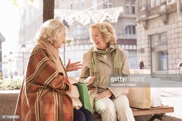sociale senioren. twee senior vrouwen nemen van een pauze van het winkelcentrum, lachen en onderzoeken van gekochte artikelen - alleen volwassenen stockfoto's en -beelden
