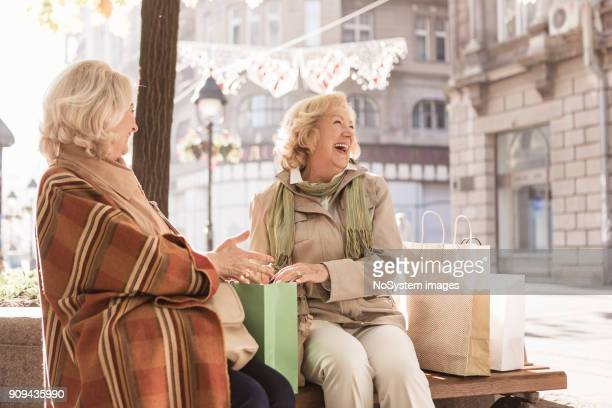 social seniors. two senior women taking a break from shopping,  laughing and examine purchased items - adults only stock pictures, royalty-free photos & images