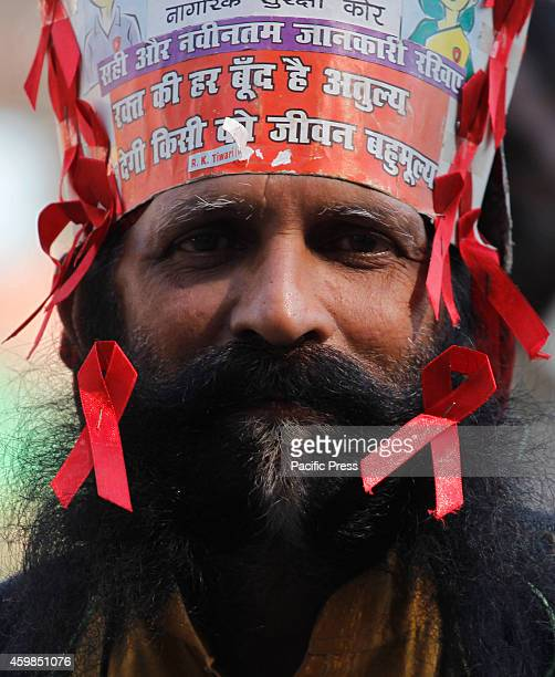 A social worker diplays red ribbon during the occasion of 'World AIDS Day' celebration in Allahabad