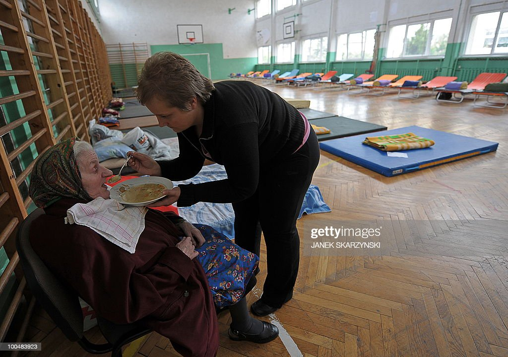 A social worker feeds an elderly woman evacuated from flooded Juliszew village in central Poland at Wisla river on May 24, 2010 in a school sport hall prepared for rescued people. Flash floods caused by heavy rainfall have hit parts of central Europe, killing at least 14 people, disrupting power supplies and forcing thousands of people from their homes.