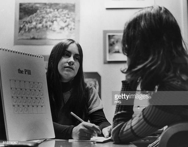 A social worker in discussion with a client in New York City circa 1970 A calendar explaining the use of the contraceptive pill is visible on her desk