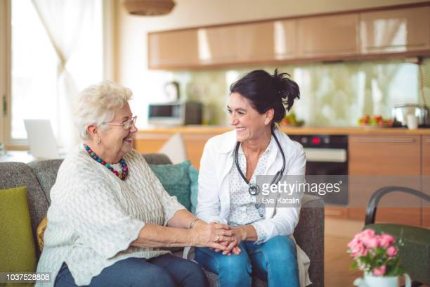 social worker is visiting a senior woman - visit stock pictures, royalty-free photos & images