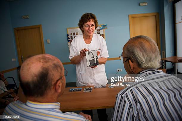 Social worker Nuria Casulleres shows a portrait of Audrey Hepburn to elderly men during a memory activity at the Cuidem La Memoria elderly home which...