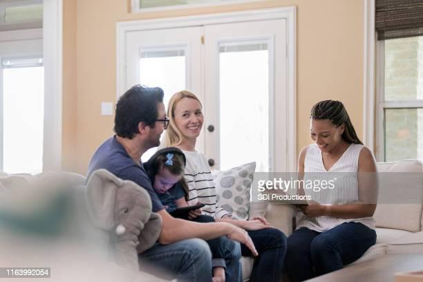 o trabalhador social fala com os pais da criança das necessidades especiais - assistente social - fotografias e filmes do acervo