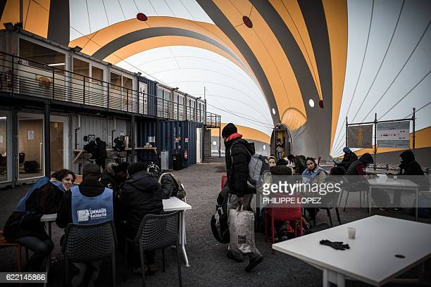 Social workers and migrants sit inside the processing center for migrants and refugees in northern Paris on November 10 the day of its inauguration /...