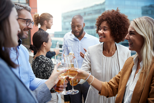 Socialising office colleagues raising glasses and making a toast with drinks after work 1146473379
