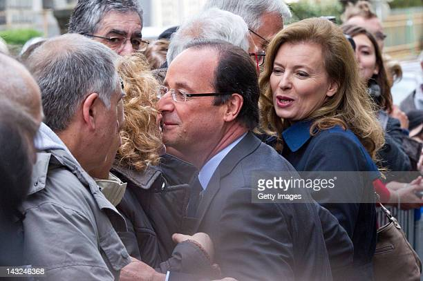 Socialist Party candidate Francois Hollande greets supporters as he arrives to cast his vote with his companion Valerie Trierweiler during the first...