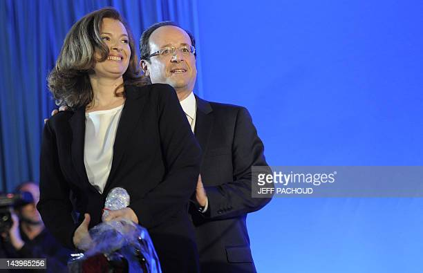 Socialist Party newly elected president Francois Hollande and his companion Valerie Trierweiler pose with roses on stage after a speech after the...