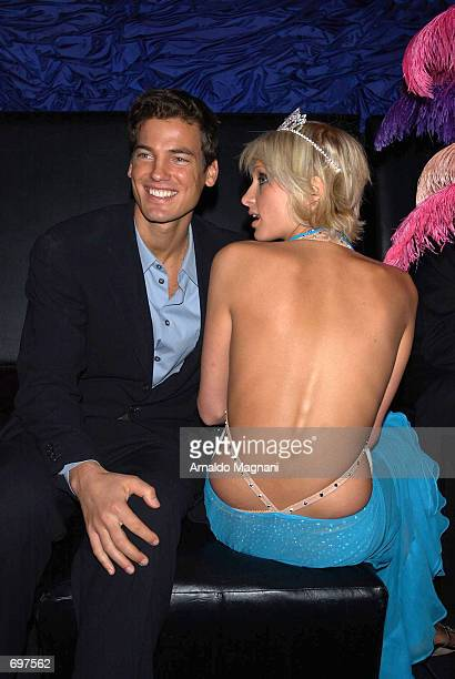 Socialite and hotel heiress Paris Hilton sits with her fiance Jason Shaw at her 21st birthday party at Studio 54 February 13 2002 in New York City