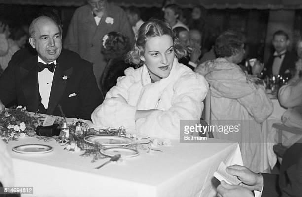 Socialite Doris Duke rests at a table wearing a white fur coat during the Green White Ball at Palm Beach's Colony Club