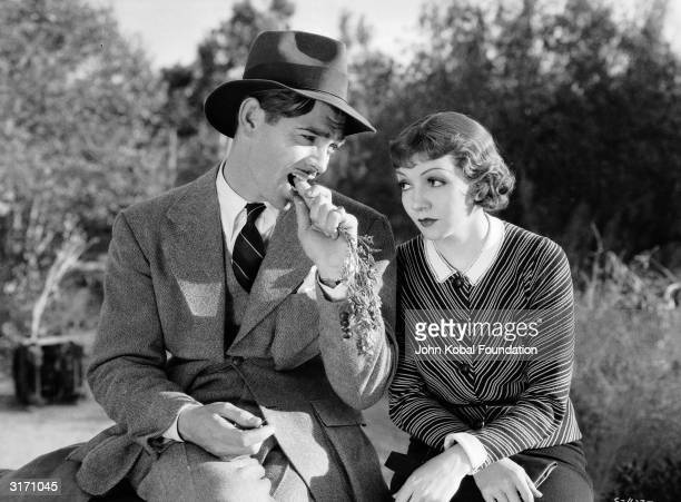 Socialite Ellie Andrews played by Claudette Colbert appears distracted while reporter Peter Warne played by Clark Gable bites nonchalantly on a...