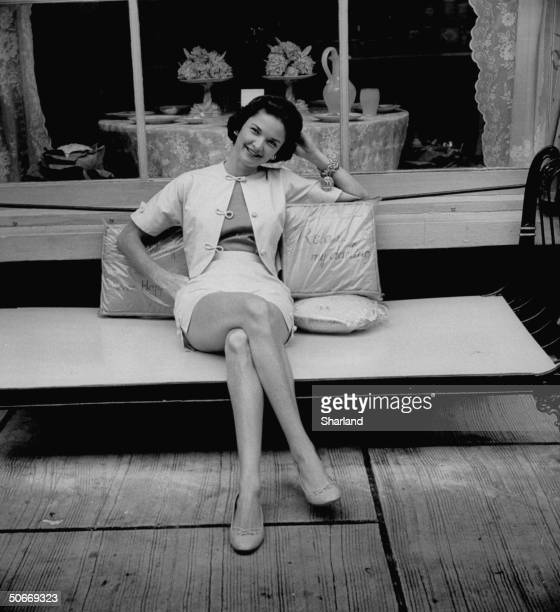 Socialite Mrs Igor Cassini sitting outside Worth Avenue shop wearing white shorts and tailored jacket with frog fastenings