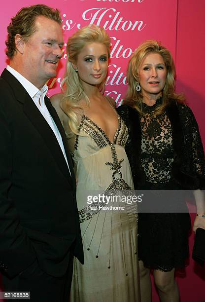 Socialite Paris Hilton poses with her parents Rick and Kathy Hilton during her fragrance launch party at Duvet during Olympus Fashion Week on...