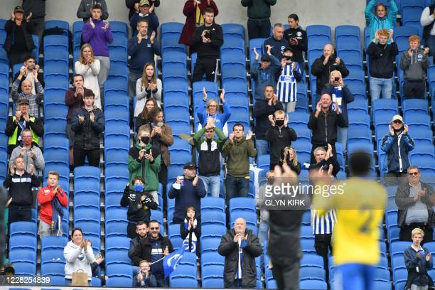 Socially distanced fans applaud players and manager from the stands after the pre-season friendly football match between Brighton and Hove Albion and...