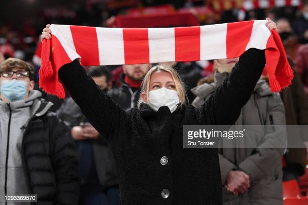 "Socially distanced female Liverpool fan sings ""You'll never walk alone"" wearing a protective face covering whilst holding a red and white scarf in..."