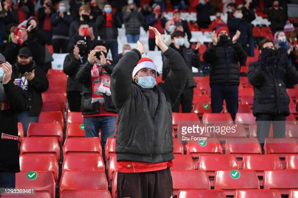 Socially distanced Liverpool fan wearing a protective face covering applauds his team from the Kop End of the gound during the Premier League match...