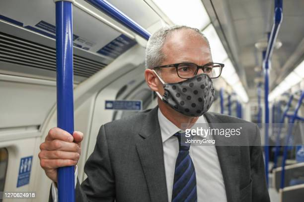 socially responsible corporate executive commuting on subway - pole stock pictures, royalty-free photos & images