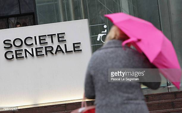 Societe Generale employee walks past the Societe Generale bank logo in front of the entrance of its headquarters on January 30 2008 in La Defense...
