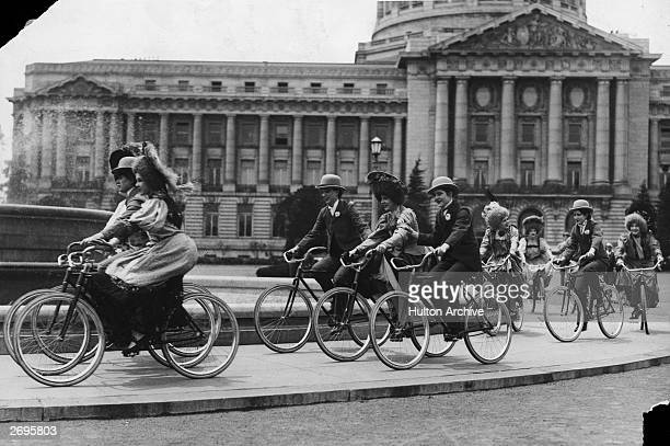 Society ladies ride bicycles around the fountain at City Hall while reenacting an old-style bicycle race in San Francisco, California. Several of the...