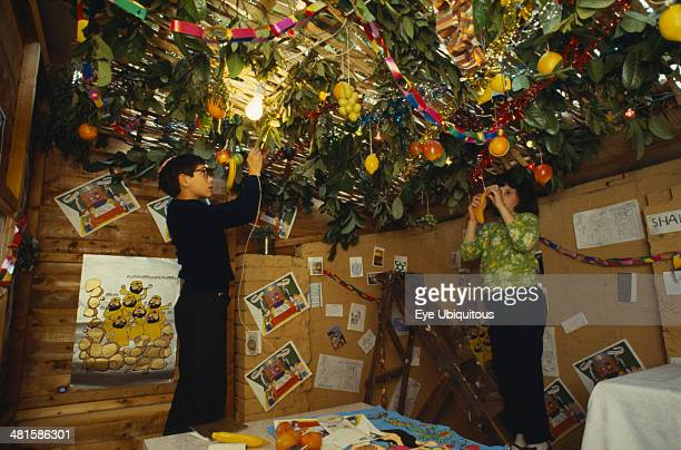 Society, Religion, Judaism, England. Jewish children decorating the ceiling of a Sukka with cut branches and fruit during the Sukkot Festival.