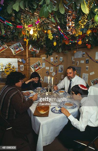 Society, Religion, Judaism, England. Jewish family eating a meal in a Sukka during the Sukkot Festival.