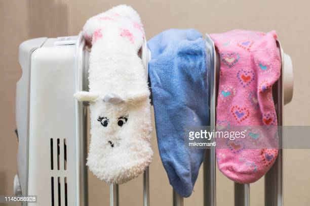 socks drying on electric heater convector at home. - sock stock pictures, royalty-free photos & images
