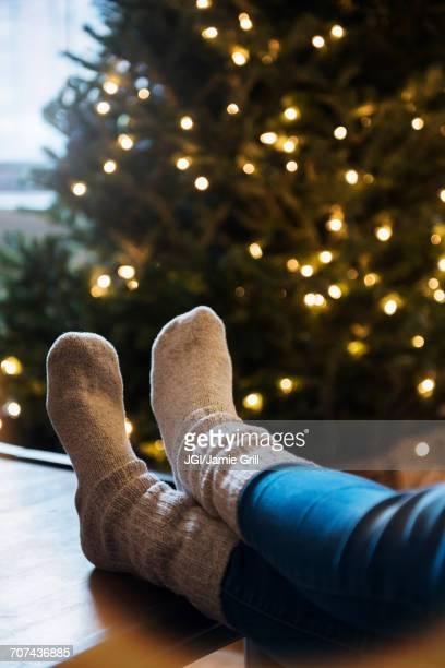Socks of Caucasian woman with feet on table near Christmas tree