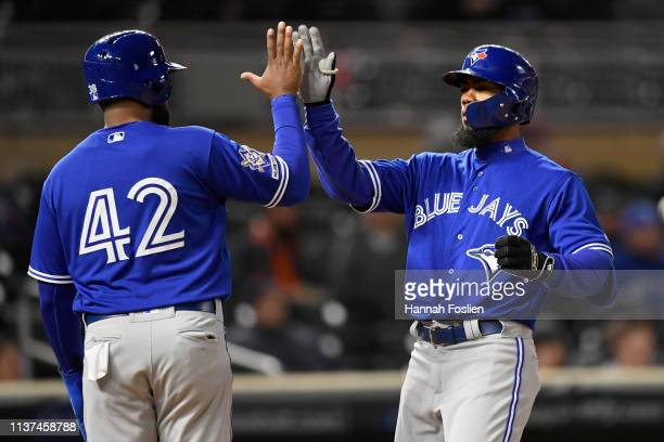Socrates Brito of the Toronto Blue Jays congratulates teammate Teoscar Hernandez on a threerun home run against the Minnesota Twins during the eighth...
