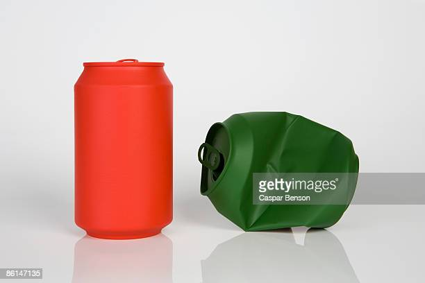 A soda can painted red and a crushed soda can painted green
