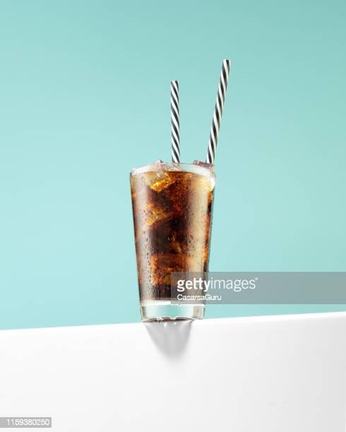 soda-drink mit eiswürfeln und wiederverwendbaren trinkhalmen - pepsi stock-fotos und bilder
