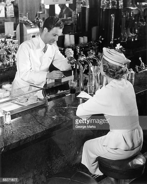 Soda fountain attendant serving young woman