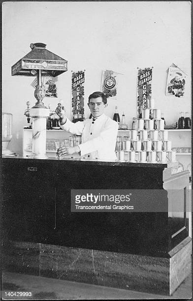 A soda jerk works at the counter in this real photo postcard from Bass Island Michigan circa 1910 Chickens