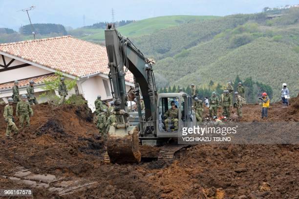 Sodats japonais effectuant des recherches pour retrouver des disparus après un tremblement de terre le 18 avril 2016, village de Minamiaso, Japon.