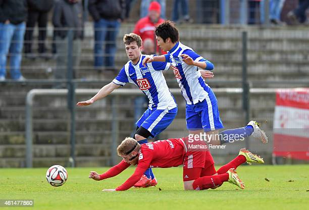 Soeren Bertram of Hallescher FC falls on the floor against Valentin Stocker and Genki Haraguchi of Hertha BSC during a Friendly Match between Hertha...