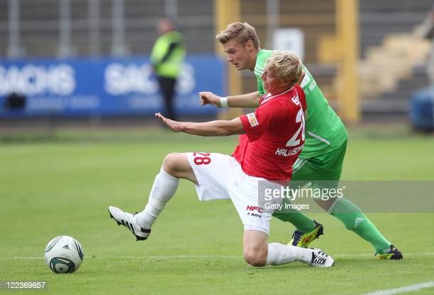 Soeren Eismann of Halle and Florian Hartherz of Wolfsburg fight for the ball during the Regionalliga North match between VfL Wolfsburg II and...