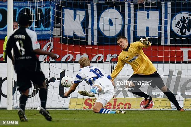 Soeren Larsen of Duisburg scores his team's first goal against goalkeeper Jan Glinker of Berlin during the Second Bundesliga match between MSV...