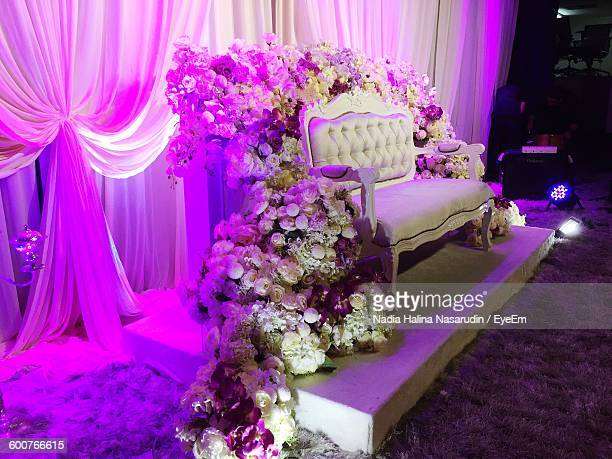 Sofa Amidst Flower Decorations On Stage In Wedding