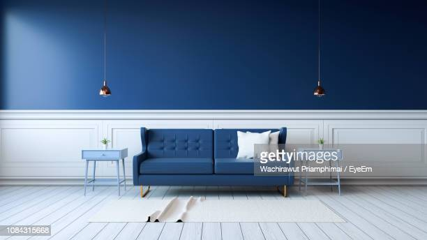 sofa amidst tables by wall at home - cushion stock pictures, royalty-free photos & images