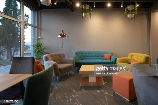 sofa and armchair in modern cafeteria - geographical locations stock pictures, royalty-free photos & images