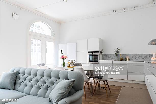 sofa by dining table at home - scandinavia stock pictures, royalty-free photos & images