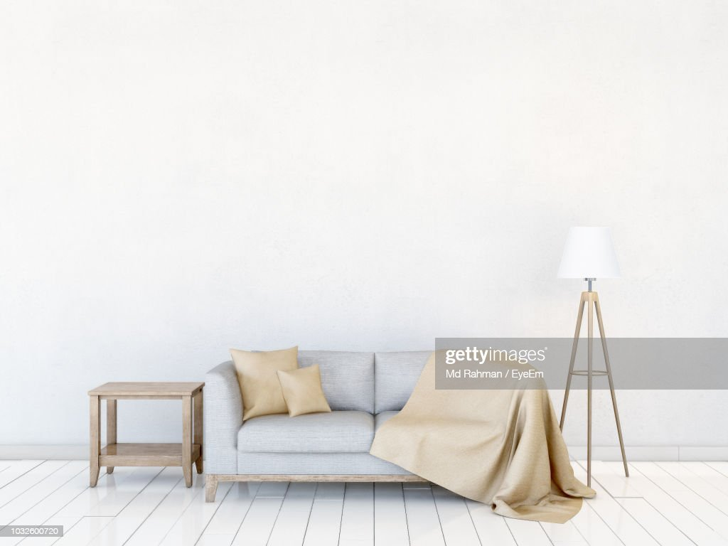 Sofa By Electric Lamp Against Wall At Home : Photo