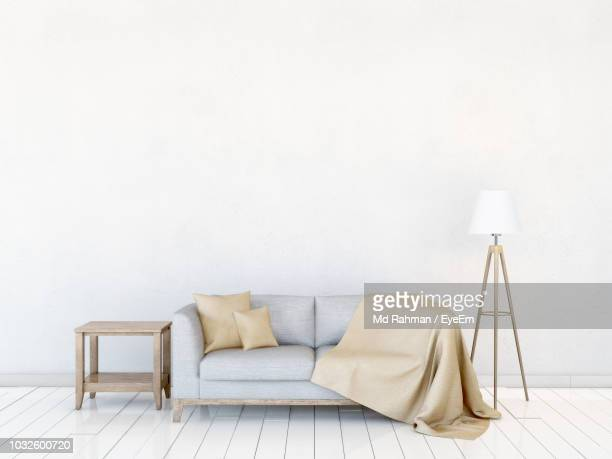 sofa by electric lamp against wall at home - divano foto e immagini stock
