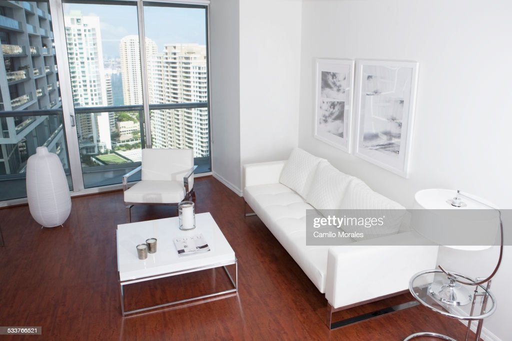 Sofa, coffee table and windows in modern apartment overlooking high rise buildings : Foto stock