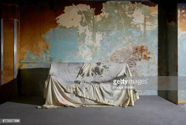 Sofa covered with dust sheet in decaying room.