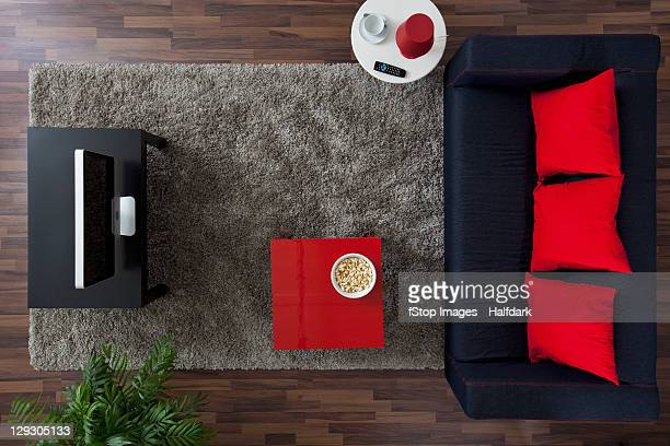 A sofa, TV and side table with a bowl of popcorn, overhead view