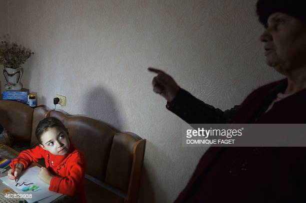 Sofia 6yearsold draws a picture while her grandmother sings a patriotic song in Donetsk's Kiyevski district in the eastern Ukraine on February 5 2015...