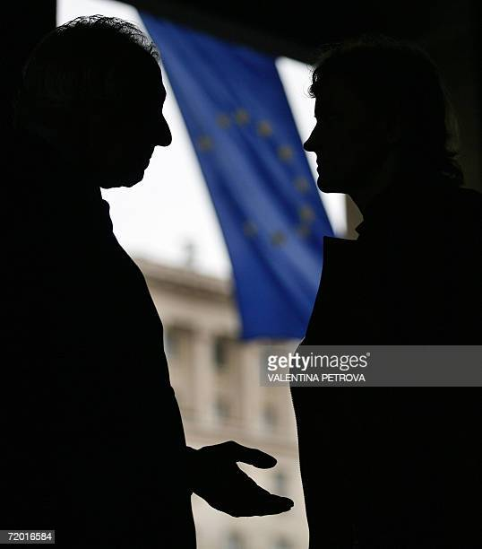 Bulgarians talk on a street in Sofia backdropped by the European Union flag 27 September 2006 European Commission president Jose Manuel Barroso and...