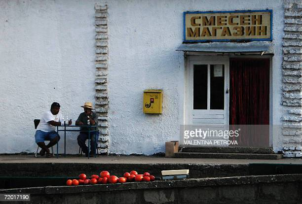 Picture taken 08 August 2006 shows villagers in front of a local jumble store talking as they sell homegrown tomatoes in the village of Varvara some...