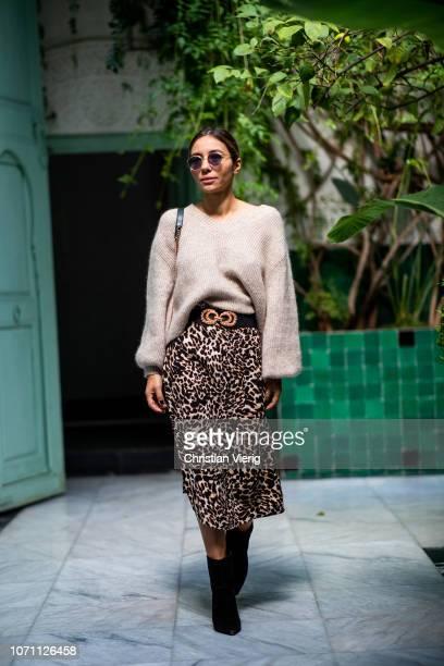 Sofia El Arabi is seen wearing midi skirt with leopard print ankle boots belt knit Chanel bag on November 29 2018 in Marrakech Morocco